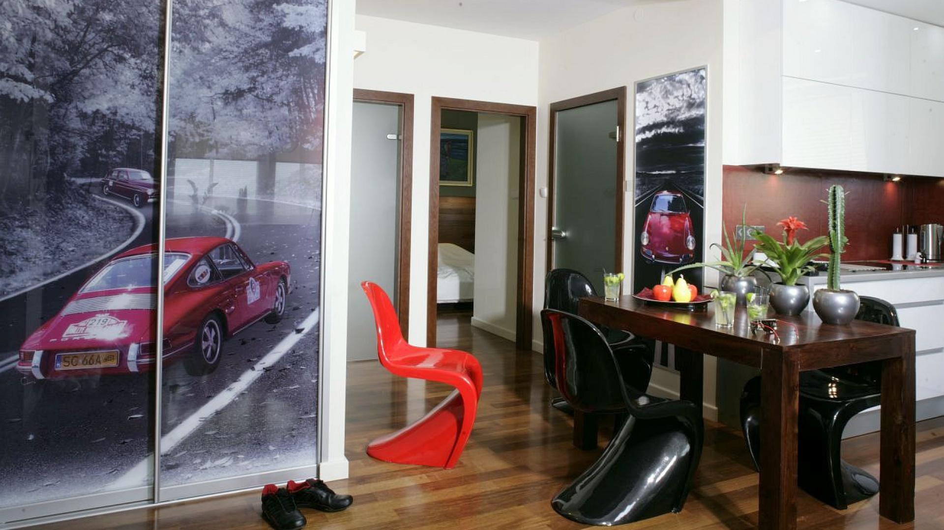 """Na styku aneksu kuchennego i salonu stanął masywny stół wykonany z drewna palisandrowego. Ciężką i prostą linię stołu odciążają nieco """"falujące"""" krzesła projektu Vernera Pantona (Verpan) oraz ogromny plakat z rozpędzonym Porsche, który dodaje wnętrzu dynamizmu i zdecydowanego, męskiego charakteru. Fot. Monika Filipiuk-Obałek."""