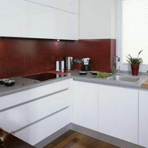 Strefa kuchenna to doskonale przemyślany mariaż delikatnej bieli oraz krwistej czerwieni w nowoczesnym, minimalistycznym wydaniu. Oszczędne w formie bryły mebli kryją wszelkie potrzebne urządzenia i sprzęty, dzięki czemu panuje tu ład i elegancja, kuchnia zaś tworzy wrażenie wtapiania się w otaczającą ją przestrzeń. Fot. Monika Filipiuk-Obałek.