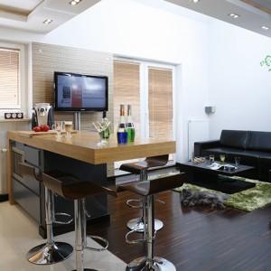 Niezwykle funkcjonalne rozwiązanie – wyspa kuchenna, która pełni różne funkcje (m.in. stółu jadalnianego), wyposażona w liczne wnęki, półki i szuflady, a także miejsce na piekarnik (Siemens). Podłogę w strefie salonu pokrywa parkiet z mozaiki przemysłowej wenge. Kącik relaksu tworzą: czarna skórzana sofa, stolik kawowy i dywan, którego oliwkowa barwa pozostaje w kontraście z ciemnym wyposażeniem i dyskretnie je ożywia. Fot. Monika Filipiuk-Obałek.