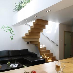 Ważnym elementem wyposażenia strefy wypoczynkowej jest sofa z ciemnej skóry, wykonana na zamówienie według pomysłu właściciela domu. Na piętro, gdzie m.in. znajduje się pokój dziecka, prowadzą jesionowe schody o przyciągającej uwagę, prostej formie. Fot. Monika Filipiuk-Obałek.