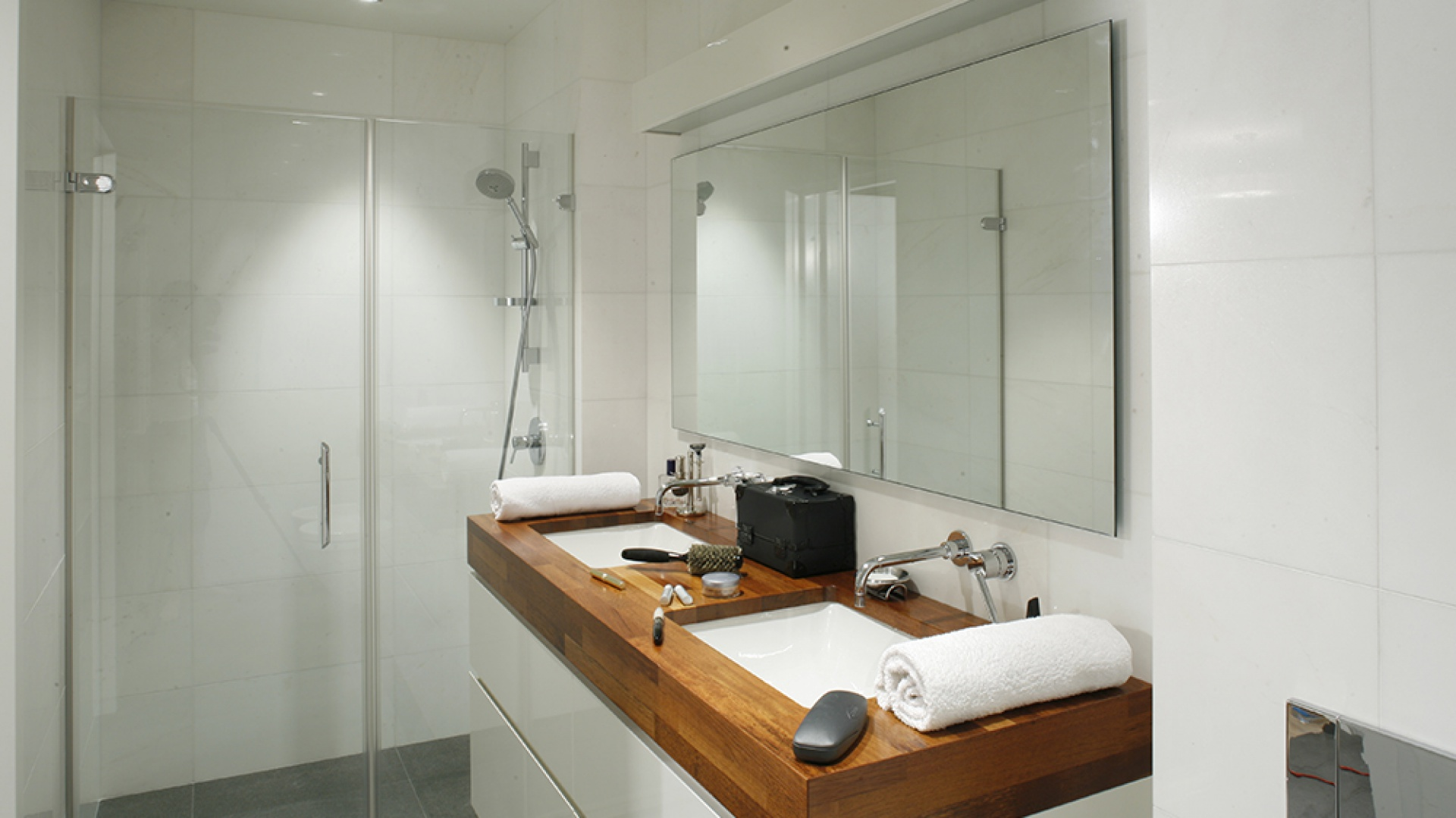 Zwężenie w głębi pomieszczenia wykorzystano jako miejsce na prysznic. Wnęka została przesłonięta taflami szkła w postaci drzwi wahadłowych i  jednej ścianki stałej (szer. wejścia 70 cm). Armatura prysznicowa z oferty firmy Zucchetti. Fot. Monika Filipiuk-Obałek.