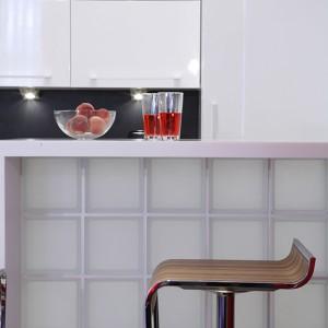 Bar – z Corianu® i matowych pustaków szklanych – pełni funkcję stolika śniadaniowego dla zapracowanego singla. Można tutaj też zaprosić gościa na drinka. Fot. Monika Filipiuk.