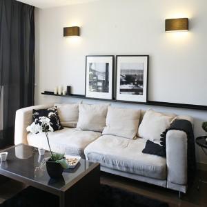 Komfortową strefę wypoczynkową tworzy w salonie piaskowa sofa oraz dwa stoliki: niski, kawowy (IKEA) i barek (Duka). Podłogę wyłożono ciepłymi w barwie panelami orzech sienna. Fot. Bartosz Jarosz.
