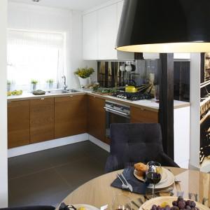 Kącik jadalniany tworzą okrągły drewniany stół (IKEA), tapicerowane krzesła oraz lampa wisząca (BoConcept). Fot. Bartosz Jarosz.