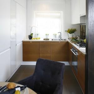 Dolne szafki w fornirze dębowym, barwionym na miodowy brąz, wnoszą ciepło do czystej, białej aranżacji. Fot. Bartosz Jarosz.
