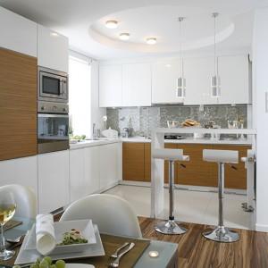 Miodowe panele zgrywają się z fornirami na szafkach mebli kuchennych, a jednocześnie wyznaczają strefę jadalni. Fot. Bartosz Jarosz.