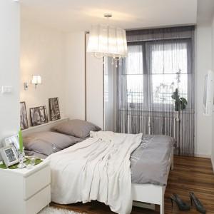 Biel sypialni zabarwiona została kroplą szarości w odcieniu zbliżonym do srebra. To nadal aura glamour, panująca w całym mieszkaniu, ale z nową nutą świeżości. Białe łóżko i szafka nocna pochodzą z IKEA, a lampa z Markslöjd. Fot. Bartosz Jarosz.