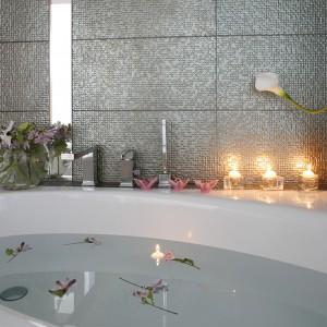 Pani domu nie odmawia sobie dekoracyjnych drobiazgów także w łazience. Wkraczają tu kwiaty, świece, piękne naczynia i kryształki. Fot. Bartosz Jarosz.