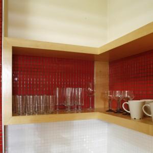 Meble kuchenne wykonano z płyty w okleinach zebrano modyfikowane i klon. Zostawienie drewna o różnych fakturach tworzy ciekawy kolaż, wzbogacony o ceramiczną mozaikę szkliwioną na kolor czerwony (Ceramika Paradyż). Fot. Bartosz Jarosz.