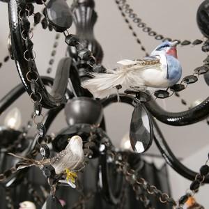 Czarny żyrandol o barokowej formie, z tworzywa na wskroś nowoczesnego,   pochodzi z Kare Design. Dziś przysiadły na nim ptaki, jednak zgodnie z porami roku dekoracje są zmieniane. Fot. Bartosz Jarosz.