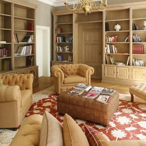 Biblioteka to miejsce wyciszone, pozwalające skupić uwagę na lekturze, albo... zapomnieć się w zaciszu miękkiego fotela czy sofy. Meble wykonane na zamówienie przez firmę Stimmebel w tkaninach przywiezionych przez panią Sylvie z Francji. Poduszki wyszukane w Sweet Home. Fot. Bartosz Jarosz.