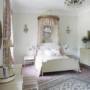 Nastrój sypialni buduje typowa francuska tkanina w scenki rodzajowe Toile de Jouy, z której uszyto zasłony, baldachim oraz narzutę na łóżko. Złotą podstawę baldachimu przywieziono z Francji i odrestaurowano, a dywan perski pani domu kupiła w Dubaju. Fot. Bartosz Jarosz.