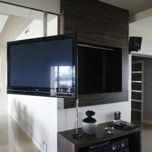 Telewizor jest przesuwany na szynie (specjalna konstrukcja projektu pana domu), Można go również obracać w dowolną stronę i oglądać z salonu lub jadalni czy kuchni. Ściana eksponująca telewizor została wykonana z naturalnego forniru hebanowego. Fot. Bartosz Jarosz.