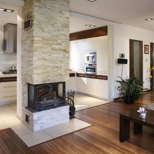 Kuchnia wizualnie łączy się z salonem: wysoka zabudowa została umieszczona we wnęce, fornir wenge nawiązuje do drewnianej podłogi i mebli w salonie. Wspólny mianownik stanowi także jednakowe oświetlenie. Fot. Monika Filipiuk-Obałek.