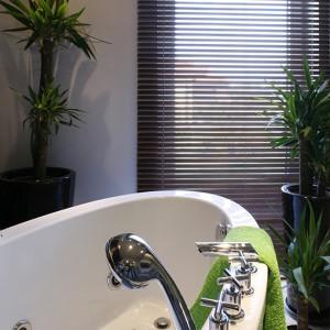 Pomalowana farbą ściana z zegarem podtrzymuje iluzję, że nie jesteśmy w łazience. Zegar pomaga też zachować umiar w korzystaniu z kąpielowych przyjemności. Fot. Monika Filipiuk.