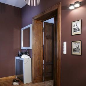Ściany przedpokoju zostały pomalowane na fioletowo-czekoladowy odcień, który pięknie harmonizuje z ciemnym kolorem drewna. Meble wykonano na zamówienie, według projektu: ramę lustra i ramę szafki stojącej wykończono matowym lakierem, fronty – ciemniejszym lakierem z połyskiem. Fot. Monika Filipiuk.