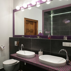 Strefa toaletowa została zaaranżowana dla dwóch osób. Na pokrytym mozaiką długim blacie umieszczono dwie umywalki Catalano (kolekcja C) oraz baterie Hansgrohe. Imponujące lustro w fioletowej, lakierowanej ramie, optycznie powiększa przestrzeń. Fot. Monika Filipiuk.