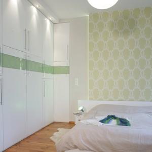Sypialnia została zaaranżowana w delikatnych odcieniach bieli i jasnej, pistacjowej zieleni. Jedna ze ścian została całkowicie zabudowana. Za frontami, pokrytymi okleiną z bielonego dębu, wyposażonymi w praktyczne stalowe uchwyty, kryje się pojemna garderoba. Fot. Monika Filipiuk.
