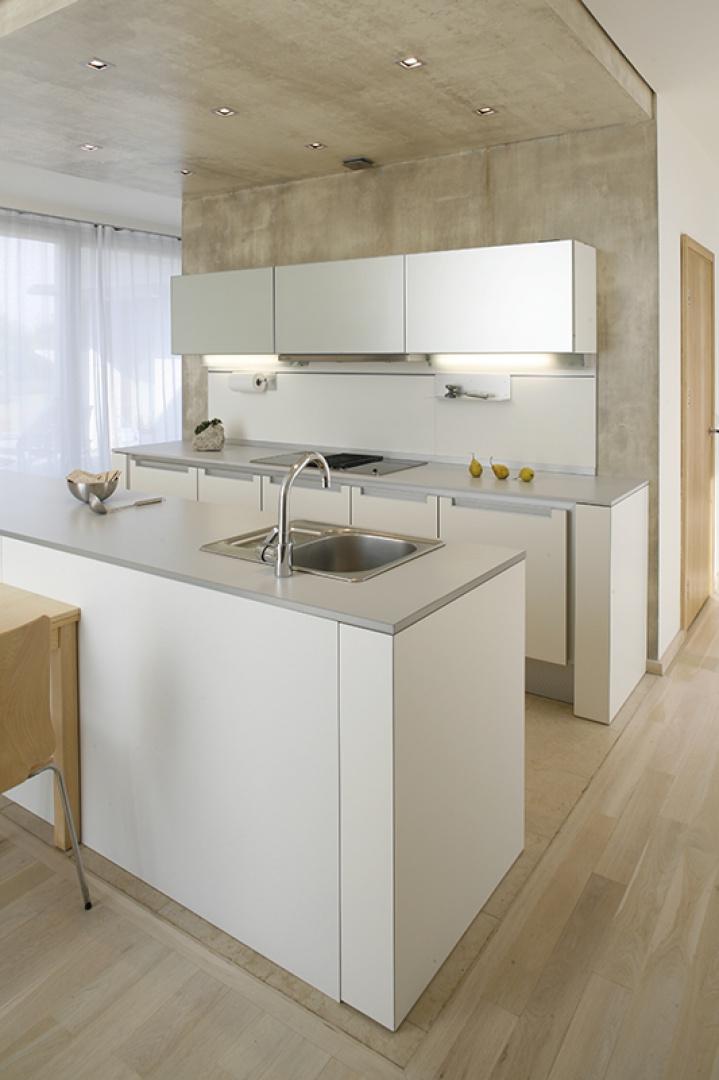 """Strefę roboczą kuchni stanowi """"wyspa"""" ulokowana w dużej przestrzeni. Symbolicznie zaznaczona jest betonową ścianą. Do kuchni prowadzą dwa przestronne przejścia. W jednym z nich znajduje się wejście do spiżarni. Fot. Bartosz Jarosz."""