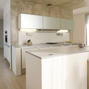 U wejścia do kuchni: ciąg szafek, kryjących lodówkę oraz piekarnik parowy Electrolux. Na podłodze – dąb bielony. Fot. Bartosz Jarosz.