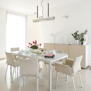 Krzesła Fino (Cor) w kremowej tapicerce skompletowano ze stołem o szklanym blacie i na stalowych nogach. Jadalnię dopełniają: komoda z kolekcji Everywhere (Ligne Roset) oraz industrialna lampa wisząca Nil (Anta). Fot. Monika Filipiuk.