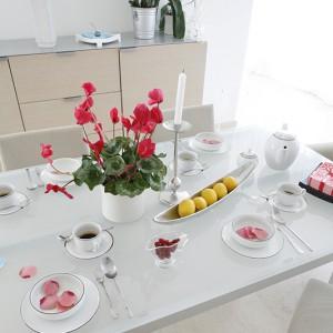 Porcelana i dekoracje odzwierciedlają dwie stylistyczne tendencje obecne w domu: delikatność oraz powściągliwą surowość. Obok eleganckiej zastawy stołowej ze srebrnym wykończeniem, stalowe naczynie na owoce. Fot. Monika Filipiuk.