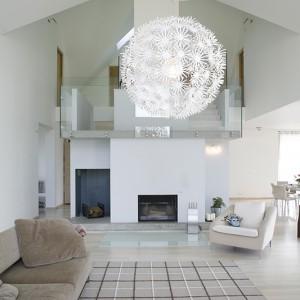 Odważną architekturę domu tworzą industrialne materiały: beton i szklana balustrada schodów, para stalowych lin biegnąca przez salon. Znacznych rozmiarów lampa-dmuchawiec z IKEA tylko wzmacnia efekt lekkości przeskalowanych form. Fot. Monika Filipiuk.