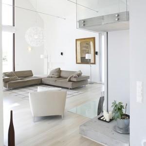 Centrum strefy relaksu w salonie tworzy sofa narożna Loft marki Arketipo. W jej najbliższym otoczeniu: fotel In Finn (Ligne Roset), dwie lampy podłogowe oraz obraz Aleksandry Herbowskiej-Matery. Fot. Monika Filipiuk.