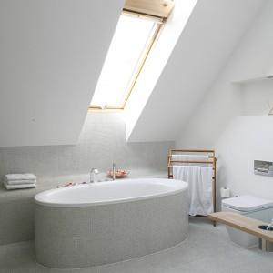 Umieszczona tuż pod skosem wanna to model dwuosobowy marki Duravit. Wpadające przez duże okno dachowe promienie słońca dodatkowo rozświetlają wnętrze, a nocne niebo stanowi idealną scenerię dla romantycznych kąpieli. Fot. Bartosz Jarosz.