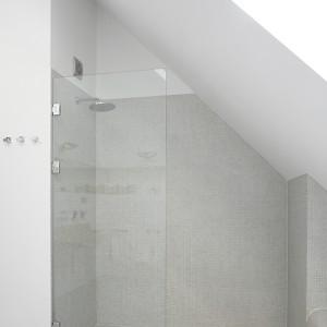 Skos ściany wyznaczył miejsce na wnękę prysznicową. Minimalistyczna kabina typu walk-in wyposażona została wyłącznie w deszczownicę. Fot. Bartosz Jarosz.
