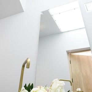 Świetlik w suficie toalety jest jednocześnie elementem szklanej podłogi na piętrze. Wpisuje się w nowoczesne rozwiązania zastosowane w całym domu. Fot. Bartosz Jarosz.