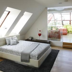 Sypialnia na poddaszu to wnętrze znacznie bardziej przytulne niż reszta pomieszczeń domu. Naturalnym ocieplaczem atmosfery jest przede wszystkim drewniana podłoga (Parador). Sporo tu również czerni: dywan Moho oraz szafa z czarnego szkła Rimadesio.