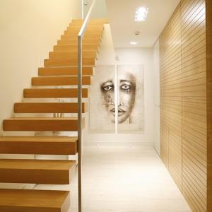 Jakby zawieszone w powietrzu stopnie drewnianych schodów, prowadzą wprost na piętro domu. W głebi korytarza: obraz Tatiany Piątek – zagadkowa, podzielona na pół twarz. Podłoga z trawertynu – eleganckie i nienarzucające się tło dla pozostałych elementów w mieszkaniu. Fot. Bartosz Jarosz.