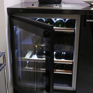 Zabudowa kuchenna z czarnego parapanu maksymalnie wykorzystuje przestrzeń niewielkiej kuchni. Pod blatem wbudowano winiarkę, a systemy szuflad kryją drobniejsze sprzęty i akcesoria kuchenne. Fot. Bartosz Jarosz.