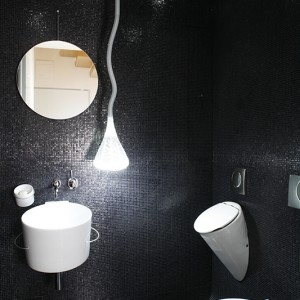 Zaskakujące miejsce – łazienka o mrocznej, a przy tym niezywkle eleganckiej kolorystyce, z mnóstwem atutów: efektowna mozaika Bisazza, nowoczesny design i   wiele interesujących, ukrytych rozwiązań. Najjaśniejszą gwiazdą tego miejsca jest wisząca lampa Pipe marki Artemide. Fot. Bartosz Jarosz.
