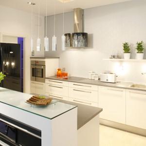 Nowoczesne meble kuchenne wykonano z laminatu. Z białą zabudową kontrastuje czarna lodówka side by side marki Whirlpool. Fot. Bartosz Jarosz.