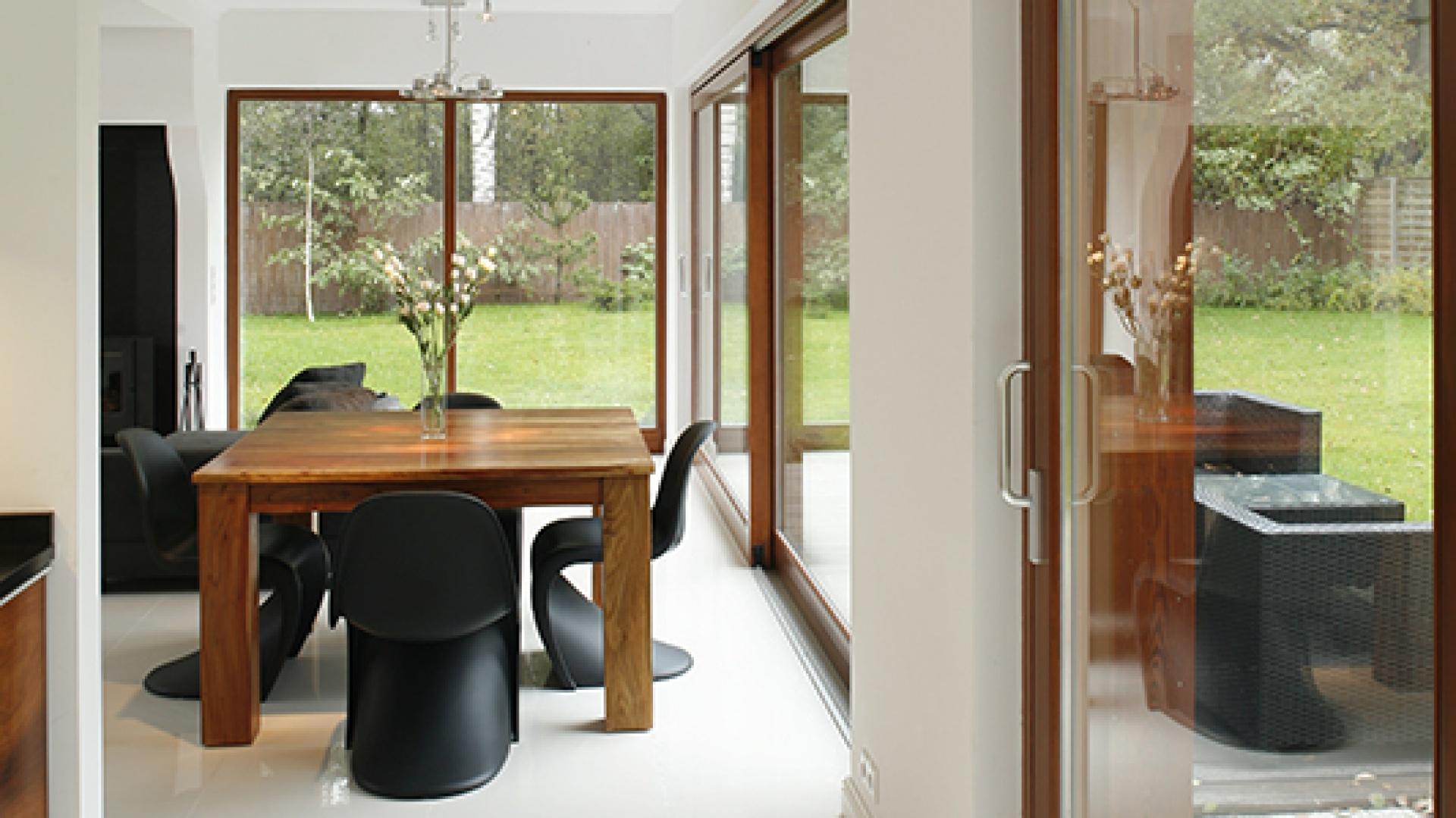 """Ogromne okna doświetlają nie tylko kuchnię, ale i jadalnię, gdzie ustawiono stół z akacji indyjskiej wraz z krzesłami """"Panton Chair Classic"""" marki Vitra. Fot. Bartosz Jarosz."""