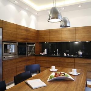 Zabudowa kuchenna gwarantuje dużą powierzchnię przechowywania oraz wygodę podczas gotowania i spożywania posiłków. Fronty meblowe, a także stół wykonane są z fornirowanej płyty (orzech). Fot. Monika Filipiuk.