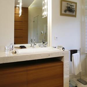 Umywalkę okala blat z trawertynu identycznego jak ten na podłodze. Umieszczona pod nim szafka na przybory łazienkowe wykonana jest z egzotycznego drewna merbau. Fot. Monika Filipiuk.