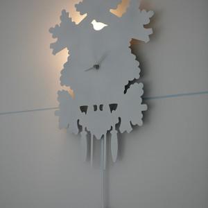 Biały zegar, prawie niewidoczny na białym tle ściany. Fot. Bartosz Jarosz.