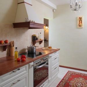 """W kuchni urządzonej w stylu wiejskim nie mogło zabraknąć okapu kominowego z drewnianą ramą (""""Ranch 60"""" firmy Faber). Płytę grzejną i piekarnik wybrano z oferty firmy Amica. Fot. Tomasz Markowski."""