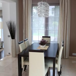 """Tapicerowane krzesła wybrała pani domu. Dzięki nim jadalnia stanowi swoisty łącznik pomiędzy kuchnią w kolorze wenge a beżowym wystrojem salonu. Nad stołem """"Birmingham"""" (Paged) efektowna lampa """"Alba"""" (Ideal Lux). Fot. Tomasz Augustyn."""