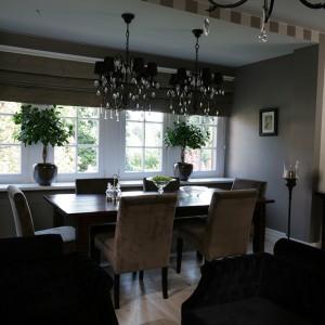 Salon i jadalnia utrzymane są w brązowo-beżowej tonacji z dodatkiem czerni, aksamitne tapicerki krzeseł i kanap zachęcają, by się w nich zanurzyć. Wnętrze oświetlają dostojne kryształowe żyrandole. Fot. Tomasz Augustyn.