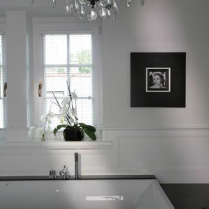 W łazience, z prostymi, nowoczesnymi kształtami ceramiki kontrastują stylowe dodatki. Całość opiera się na połączeniu czerni i bieli. Rolę niebanalnej dekoracji pełnią m.in. zdjęcia gwiazd ze świata filmu. Fot. Tomasz Augustyn.