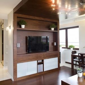 Wykończenie podwieszanego fragmentu sufitu drewnem było pomysłem inwestorów, architekt zaproponowała kontynuację takiego wykończenia także na ścianie działowej i podłodze. Na granicy kuchni i salonu zaaranżowano jadalnię. Fot. Tomasz Markowski.
