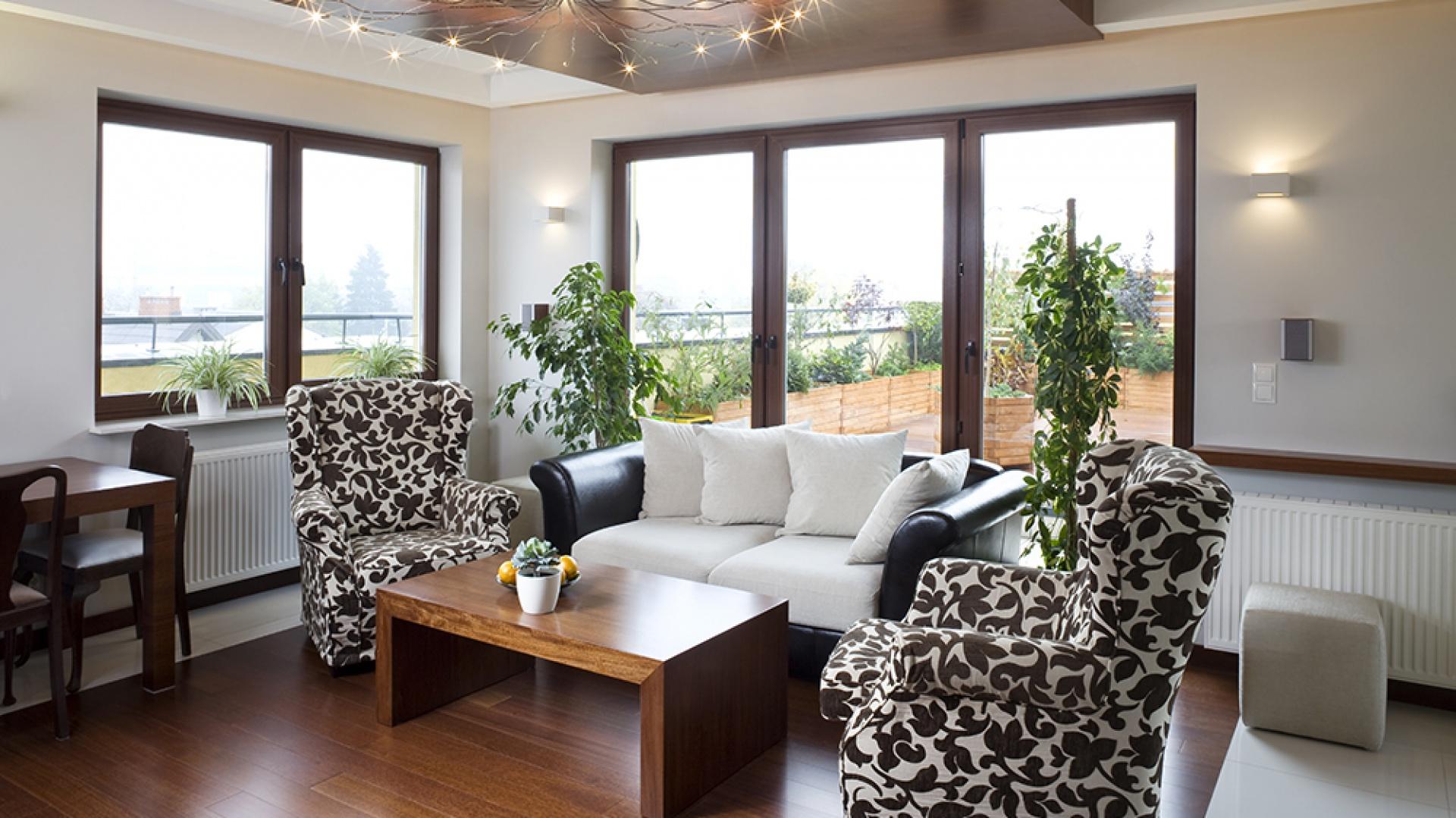 Meble w salonie dobrano tak, by harmonizowały z kolorystyczną dominantą. Oba fotele (podobnie jak kanapa, należące do wcześniejszego wyposażenia gospodarzy) zyskały nową tapicerkę w roślinny wzór. Podłoga w głównej części salonu została wyłożona drewnem. Fot. Tomek Markowski.