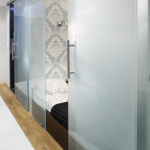 Intymne strefy: sypialnia i łazienka, wydzielone są od korytarza ściankami oraz drzwiami przesuwanymi z satynowego szkła. Fot. Bartosz Jarosz.