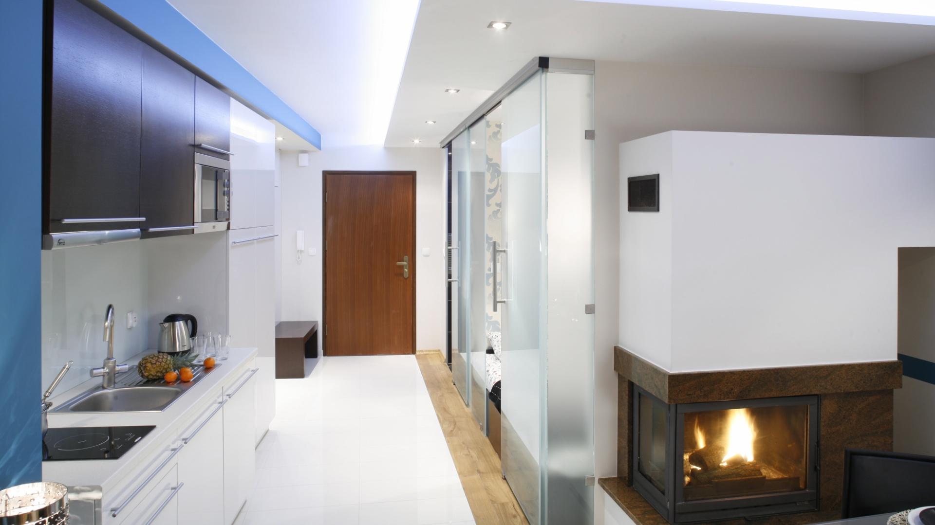 Podział stref funkcjonalnych wyraźnie widoczny jest na podłodze. W salonie i sypialni –  położono ciepłe drewno, w kuchni – białe płytki. Fot. Bartosz Jarosz.