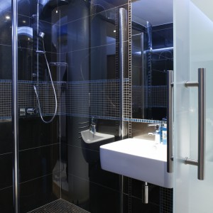 Prysznic (Ronal) o lekkiej formie, bez brodzika, jedynie symbolicznie zaznacza się w przestrzeni łazienki. Bateria prysznicowa – marki Tres. Fot. Bartosz Jarosz.