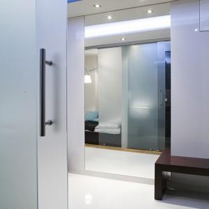 Przestrzeń powiększają jasne, efemeryczne materiały: białe satynowe szkło, duże lustra, biały gres polerowany (Amadeoceramica). Fot. Bartosz Jarosz.